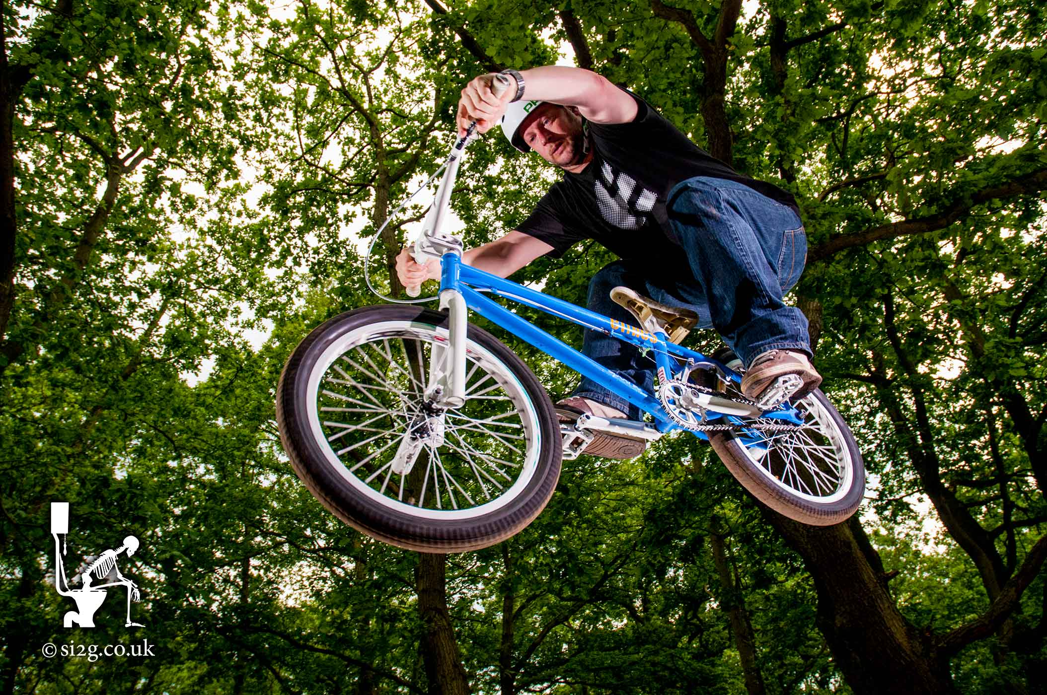 BMX-Riding Skatepark Builder - Anthony Ramsey and his team of skatepark builders also double as their own crash-test dummies.  Anthony catches air on his BMX in the cool-shade of a UK forest.