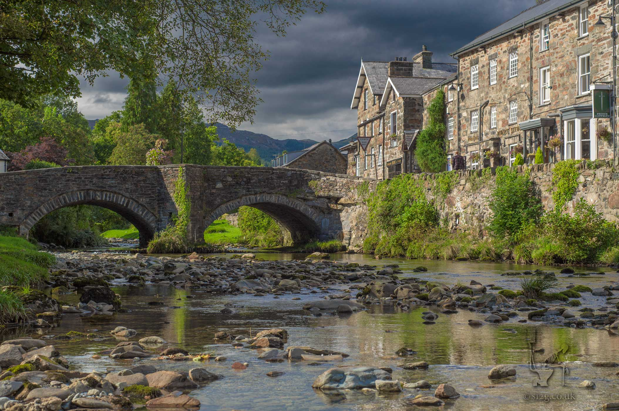 Chocolate Box Village - This picturesque stone bridge and country pub is situated in the village of Beddgelert in Snowdonia, Wales.  Wanting to get an edge over the other photographers milling around that day, I decided to climb over the stone wall paddle about in the river to get that chocolate box image of serenity with no cars or people in shot.