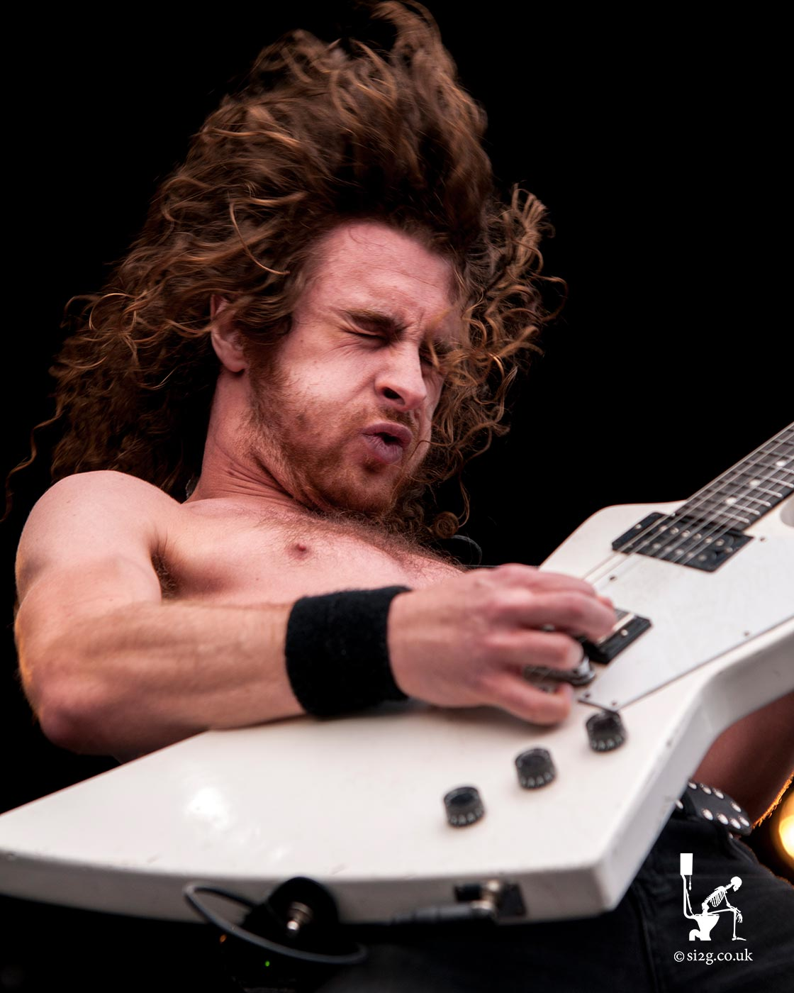 Airbourne - Joel OKeeffe, vocalist and lead guitarist for Australian hard rock band Airbourne, commands the Download Festival to rock to the tune of his white Gibson Explorer guitar.  Hidden between his fingers is the legendary Pick of Destiny, an evil yet powerful guitar plectrum used by all the greatest rock musicians.